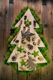 Christmas tree decorated with natural material from the forest. Handmade christmas tree of wood on wooden background with natural decoration of the forest Stock Photos