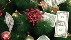 Paper money on a Christmas tree. Christmas tree decorated with paper dollars and Christmas toys stock footage