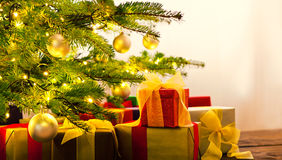 Christmas tree decorated with presents. In living room Stock Image