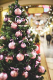 Christmas tree decorated purple balls. Christmas tree decorated with purple balls standing in lobby of store, toned photo Royalty Free Stock Photography