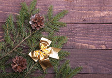 Christmas tree decorated red bow, branches and cones on wooden background Stock Photography