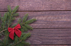 Christmas tree decorated red bow, branches and cones on wooden background Stock Photo