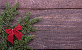 Christmas tree decorated red bow, branches and cones on wooden background Stock Photos