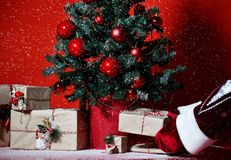 Christmas tree decorated with red patchwork ornament balls and santa claus hands put craft presents gifts. Under new year 2019 tree heavy snow on dark red royalty free stock photography