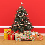 Christmas tree decorated in a red room with gift packs. Christmas Scene: beautiful gift packs rest at the foot of a beautiful Christmas tree decorated in a Stock Images