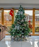 Christmas tree decorated with silver bows and baubles. Beautiful tall Christmas tree decorated with silver bows and baubles Stock Photos