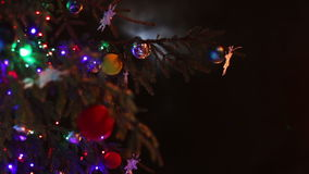 Christmas tree decorated with toys and lights at. Decorated in different lights, toys, snowflakes Christmas tree standing in the street and sways in the wind in stock footage