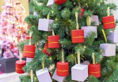 The Christmas tree is decorated with various gifts in small boxes stock photos