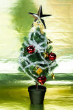 Christmas tree decorated wiith ornaments in rich gold shiny background - full length Royalty Free Stock Photography