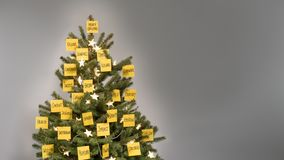 Christmas tree decorated with 25 yellow post-it notes with business keywords and wishes. Christmas tree with decorations of 25 yellow post-it notes with business royalty free stock images