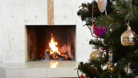 Christmas tree with decoration on background of burning fireplace stock video footage