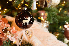 Christmas tree decoration ball with deer, stars and pine cones, feathers. Spruce branches bokeh lights. Background. Christmas decoration with toy deer, balls and Royalty Free Stock Photo