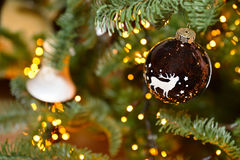 Christmas tree decoration ball with deer, stars and pine cones, feathers. Spruce branches bokeh lights. Background. Christmas decoration with toy deer, balls and Stock Images