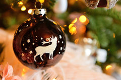 Christmas tree decoration ball with deer, stars and pine cones, feathers. Spruce branches bokeh lights. Background. Christmas decoration with toy deer, balls and Royalty Free Stock Photography