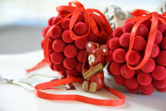 Christmas tree decoration balls and wooden bear. Holding golden gift Royalty Free Stock Images