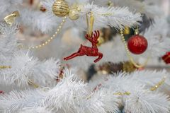 White Christmas tree decorated with yellow and red toys royalty free stock photo