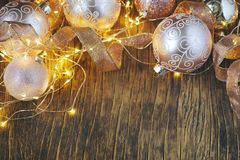 Christmas tree decoration glass balls and light garland over rustic wooden background. Stock Photo