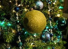 Christmas tree decoration. Glittery green bulb on a pine tree with blue lights Royalty Free Stock Images