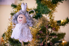 Christmas tree decoration. Smiling angel in white lacy dress with crown on a Christmas tree with touches of gold and green needles stock images