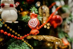 Christmas tree decoration toy in the form of a cute red candy. On the background of fir tree Royalty Free Stock Photo