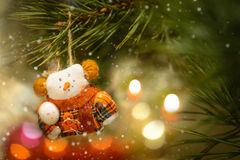 Christmas Tree Decoration With Toys Snowman. Toy Snowman In The Warm Clothing on The Christmas Tree and Decoration Candle Light Stock Photos