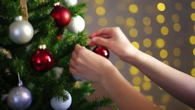 Woman putting ornament on Christmas tree in decorated room stock video