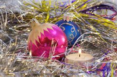 Christmas tree decorations. Two round christmas tree toys among decorations and a candle royalty free stock image