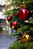 Christmas tree and decorations. Close up of a Christmas tree and its colourful decorations. Shallow depth of field. Cobbled street in the background, with Stock Images