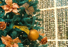Christmas tree decorations. Fragment of christmas tree with gilt ball and flowers royalty free stock image