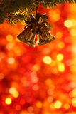 Christmas tree decorations. Christmas bells on branch of fir-tree against blurred background stock images