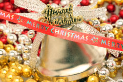 Christmas tree decorations. Merry Christmas ribbon in front of bell and beads Stock Images