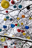 Christmas tree decorations. Colorful Christmas baubles hung from branches of snowy tree outdoors royalty free stock image