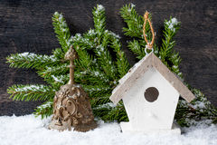 Christmas tree Decorations: birdhouse and the bell on the vintage background Stock Images