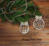 CHRISTMAS-TREE DECORATIONS ON THE FESTIVE FIR-TREE  WITH THE INSCRIPTION OF THE MERRY CHRISTMAS. CHRISTMAS-TREE DECORATIONS ON THE FESTIVE FIR-TREE ON THE WOODEN Stock Image