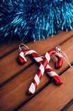 Christmas tree decorations in the form of candy cane on wooden t. Christmas candy cane on wooden table Stock Photo