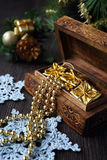 Christmas-tree decorations and goldish garland in carved wooden Royalty Free Stock Photography