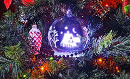 Christmas tree decorations hang on fir-tree branches. Stock Photos