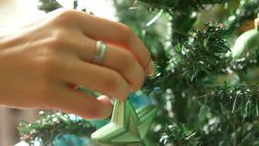 Christmas tree decorations for the New Year. The New Year`s star is hung on a tree. stock video footage