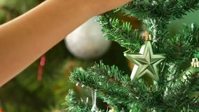 Christmas tree decorations for the New Year. The New Year`s star is hung on a tree. stock footage