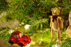 Christmas tree decorations. Small red car hanging on xmas tree. Teddy bear with red bow. Royalty Free Stock Photography