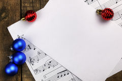 Christmas tree decorations on the table and sheet with music not Stock Photos