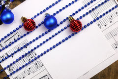 Christmas tree decorations on the table and sheet with music not Stock Photography