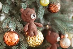 Christmas tree decorations. Toy knitted bear and vintage balls on cristmas tree. Close up shot.  Stock Image