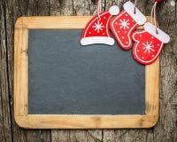 Christmas tree decorations on vintage wooden blackboard Stock Photos