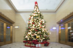 Christmas Tree with Decorations and Wrapped Gifts Bokeh stock image