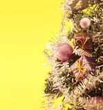Christmas tree with decorations on yellow background Stock Photo