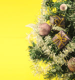 Christmas tree with decorations on yellow background Royalty Free Stock Images