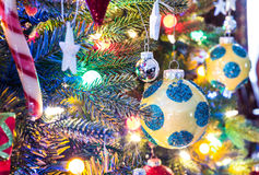 Christmas tree decorations.  Yellow, shiny finish, orb with blue circles, glows, surrounded by bright vibrant multicoloure lights. Royalty Free Stock Image