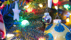Christmas tree decorations.  Yellow, shiny finish, orb with blue circles, glows, surrounded by bright vibrant multicoloure lights. Royalty Free Stock Images
