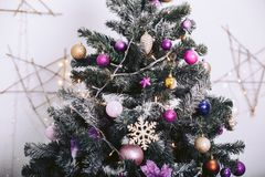 Christmas tree with decorative toys and garlands in the background. Christmas tree with decorative toys and garlands in the shape of a star in the background royalty free stock photos